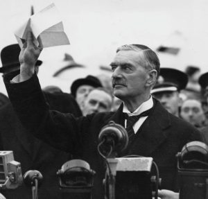 British Prime Minister Neville Chamberlain arrives at Heston Airport, returning from a meeting with Adolf Hitler in 1938, bearing